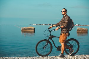 Young traveler man with a backpack in sunglasses walking on coast morning with his bicycle