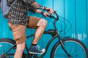 Unrecognizable young male traveler along a blue wall with a bicycle