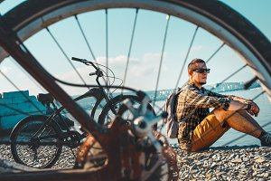 Handsome young man cyclist in sunglasses with a backpack sitting on the seashore and enjoying the sea view while relaxing, against a backdrop of a bicycle and a bicycle wheel close-up