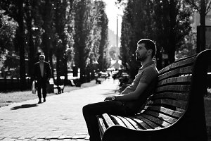 Young sad man sitting on the bench