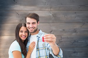 Composite image of happy young couple holding new house key