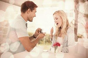 Man proposing marriage to his shocked blonde girlfriend