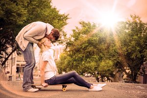 Hip young blonde sitting on skateboard with boyfriend kissing forehead