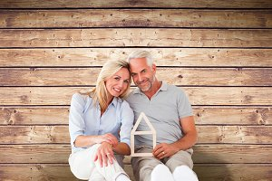 Composite image of happy couple sitting and holding house outline
