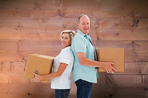 Composite image of happy older couple holding moving boxes