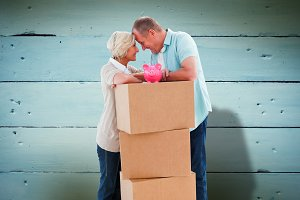 Composite image of older couple smiling at each other with moving boxes and piggy bank