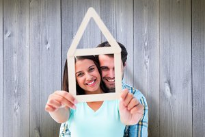 Composite image of happy young couple with house shape