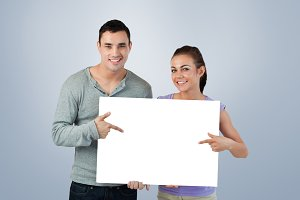Composite image of smiling young couple pointing at sign they are holding