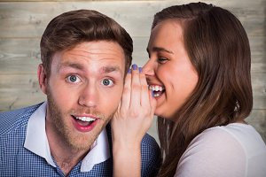 Composite image of woman whispering secret into friends ear