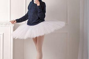Ballerina in warm sweater drink tea