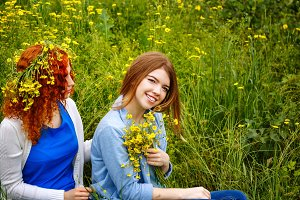 Girlfriends with flowers in park.
