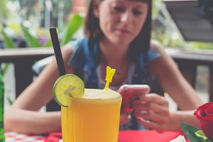 Glass of fresh orange juice with slice of lime on red background in restaurant. Tropical Bali island, Indonesia. Young woman with smartphone on a blurred background.