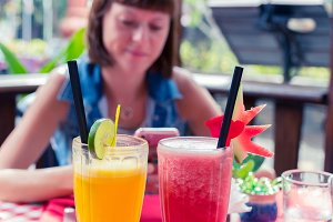 Iced fresh watermelon and orange juices glasses on a red table in restaurant and cafe interior. Tropical island of Bali, Indonesia. Young woman on a background.
