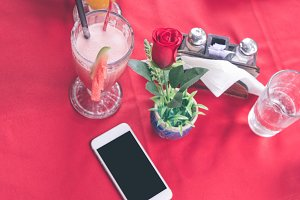 Mockup image of white mobile phone with blank white screen on red background in restaurant. Tropical Bali island, Indonesia.