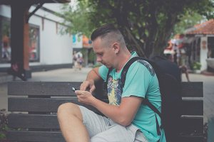 Happy young handsome man sitting on the bench outdoors and using smartphone. Tropical island of Bali, Indonesia.