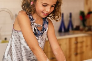 Little girl kneading dough.