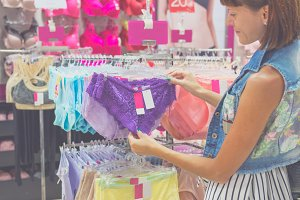 Young beautiful woman shopping, standing in the mall, choosing new lilac underwear panties, looking at fabric or price label. Bali island.