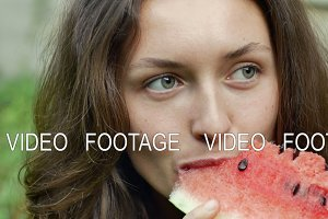Beautiful young woman is eating watermelon with pleasure and look at camera