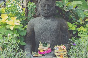 Stone Buddha statue among nature in the park of Bali island, Indonesia.