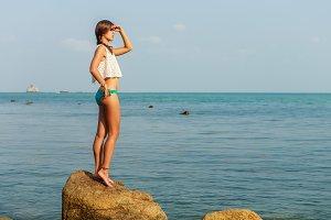 Beautiful woman stay at stone beach.
