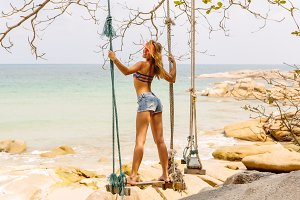 Beautiful woman posing in swings.
