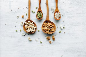 wooden spoons with seeds and nuts on the white table