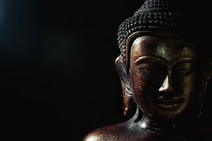 Wooden bronze buddha on black blurred background close up