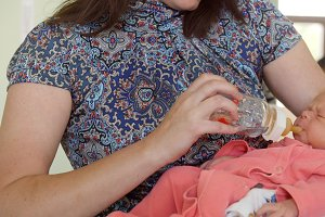 Newborn baby in maternity hospital - mother feeds her baby