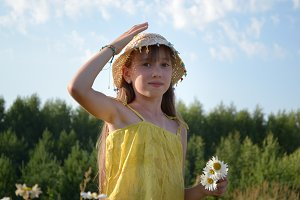 Portrait of beautiful teen girl at summer meadow, collecting flowers