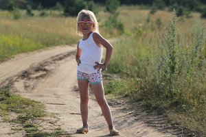 Blonde little child girl in sunglasses standing on summer dusty rural road