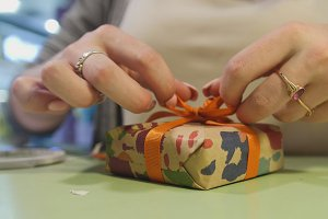 Wrapping gift - close up view woman's hands