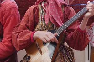 Folk music russian ensemble - woman in Russian folk costume playing the balalaika