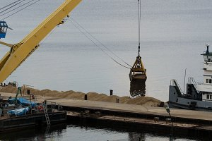 River cargo crane - process of loading sand from the barge to the ship
