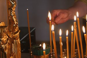 The parishioner put a candle inside an Orthodox church