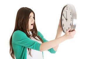 Surprised woman holding a clock