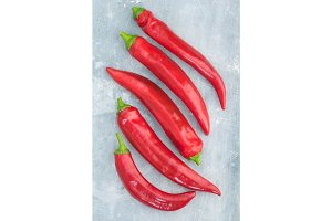 Top view of fresh red hot chili peppers on a blue textural background.