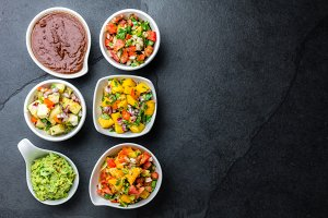 Traditional famous mexican sauces chocolate chili mole poblano, pico de gallo, avocado guacamole, salsa bandera, pinapple salsa, mango salsa on slate gray background
