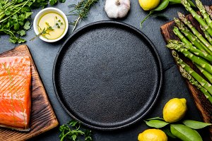 Raw salmon fillet, asparagus, lemons and herbs around cast iron plate. Food cooking background with copy space. Top view.