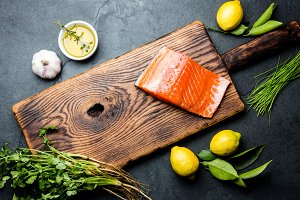 Raw salmon fillet, asparagus, lemons and herbs on wooden board. Food cooking background with copy space. Top view.