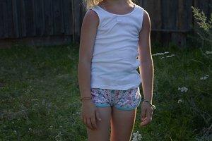 Portrait of little blonde girl posing in farm yard, summer village, sunset