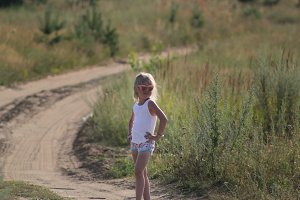 Cute little child girl in sunglasses standing on summer dusty rural road