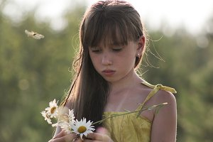 Cute girl collects flowers on field - russian summer village, close up