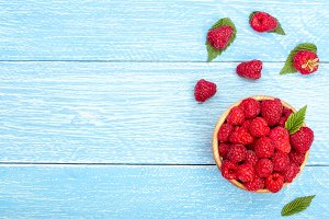 Raspberries in a bowl on the blue wooden background with copy space for your text. Top view