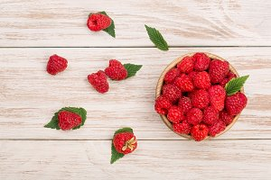 Raspberries in a bowl on the light wooden background. Top view