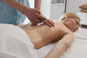 Massage for attractive blonde young woman in spa room