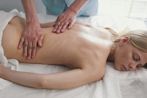 Spa. Massage for blonde woman model - man's hand on girl's back