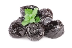 heap of dried plums or prunes with a mint leaf isolated on white background