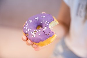 Woman's hand takes a blueberry donut