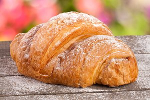 croissant sprinkled with powdered sugar on a wooden board with a blurry garden background