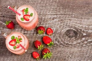 Glass of strawberry yogurt or smoothie with mint leaves on old wooden background with copy space for your text. Top view
